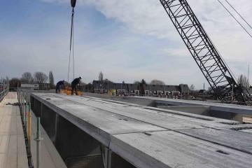 Plaatsen van prefab betonskeletten op de bouwlocatie
